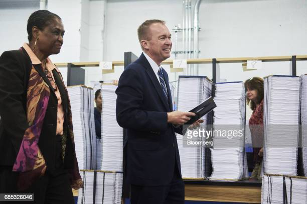 Mick Mulvaney director of the US Office of Management and Budget right holds a copy of the fiscal year 2018 budget appendix while walking with Davita...