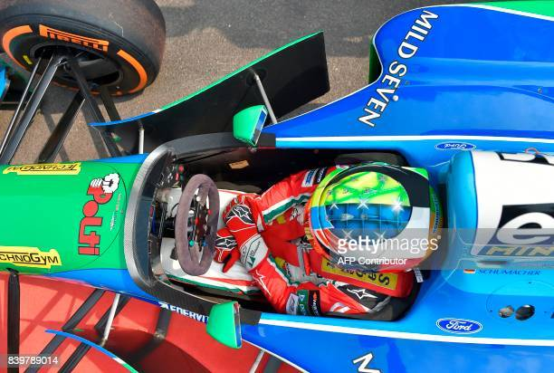 Mick Schumacher German racing driver and son of seventime Formula One champion Michael Schumacher sits inside a Benetton B194 car before driving...