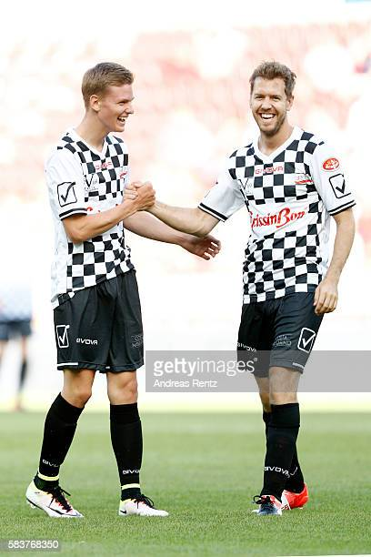 Mick Schumacher son of Michael Schumacher greets Sebastian Vettel during the 'Champions for charity' football match between Nowitzki All Stars and...