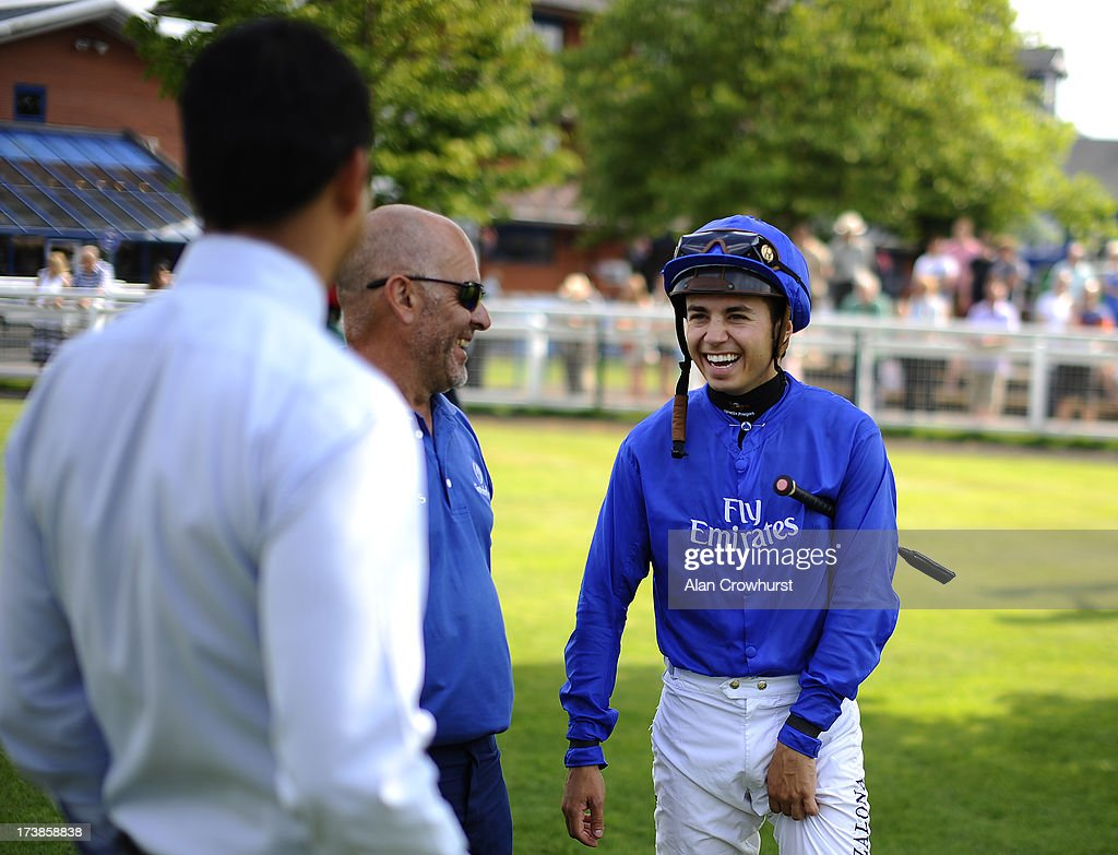 Mickael Barzalona share a joke with connections at Leicester racecourse on July 18, 2013 in Leicester, England.