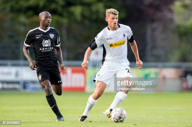 Mickael Cuisance of Borussia Moenchengladbach is chased by Jean Thierry Lazare Amani of KAS Eupen during the friendly match between KAS Eupen and...