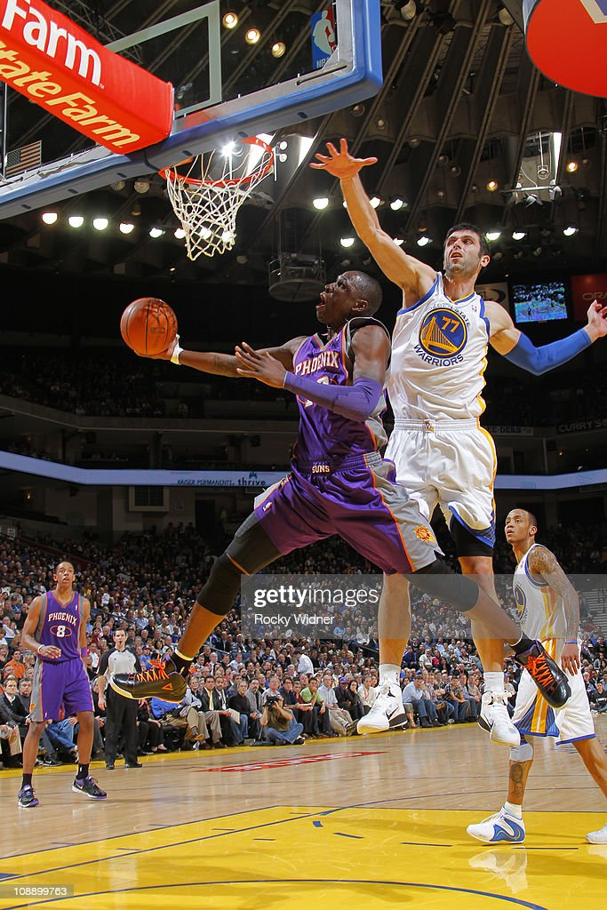 Mickael Pietrius #12 of the Phoenix Suns reaches for a layup after ducking under <a gi-track='captionPersonalityLinkClicked' href=/galleries/search?phrase=Vladimir+Radmanovic&family=editorial&specificpeople=201834 ng-click='$event.stopPropagation()'>Vladimir Radmanovic</a> #77 of the Golden State Warriors on February 7, 2011 at Oracle Arena in Oakland, California.