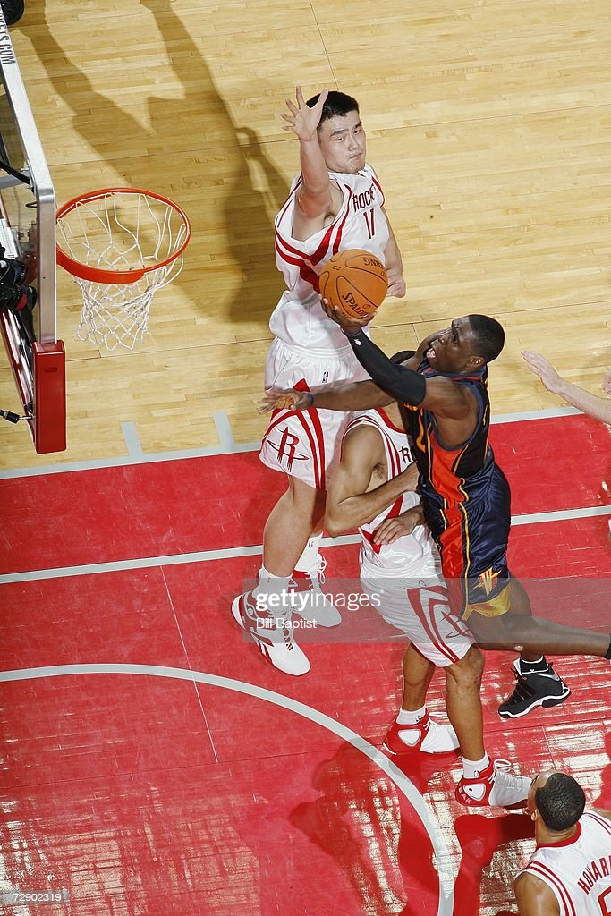 Mickael Pietrus of the Golden State Warriors shoots with contact against Shane Battier of the Houston Rockets at the Toyota Center on December 5 2006...