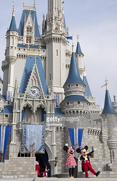Mickey and Minnie Mouse wave goodbye after a meet and greet with guests in front of the Cinderella's castle at Walt Disney World' Magic Kingdom in...