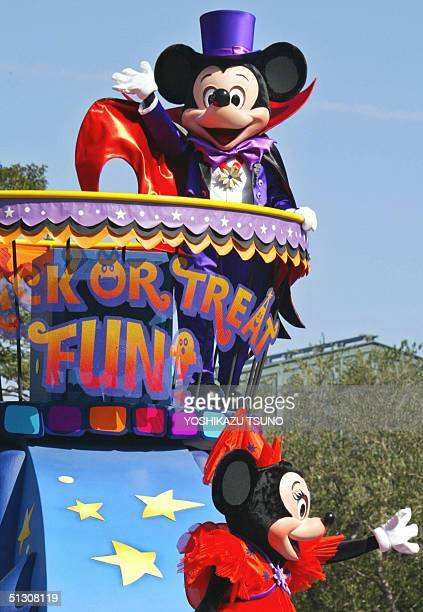 Mickey and Minnie Mouse wave to guests from a float during a Disney Halloween Parade at Tokyo Disneyland in suburban Tokyo 15 September 2004 as part...