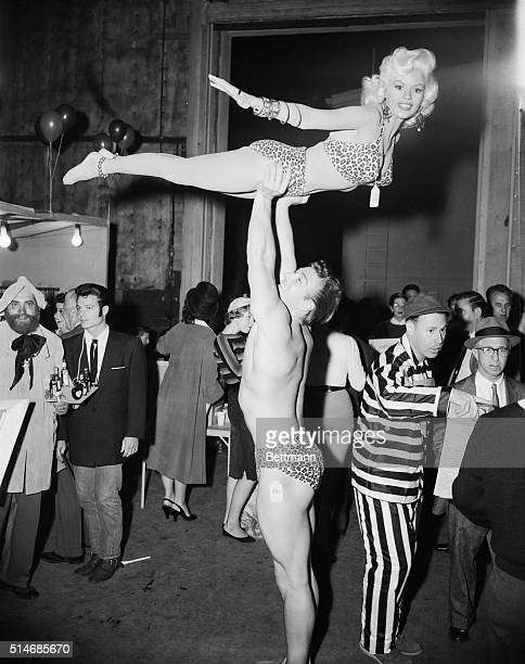 Mickey Hargitay holds his wife pinup star Jayne Mansfield high above him on October 30 1956 They are dressed in leopard print bathing suits for the...