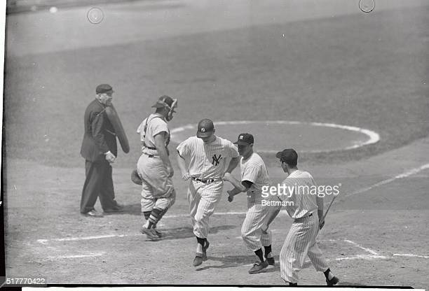 Mickey Mantle is greeted at the plate by Yankee teammate enos slaughter who was scored by the roundtripper in the second inning of today's opener of...