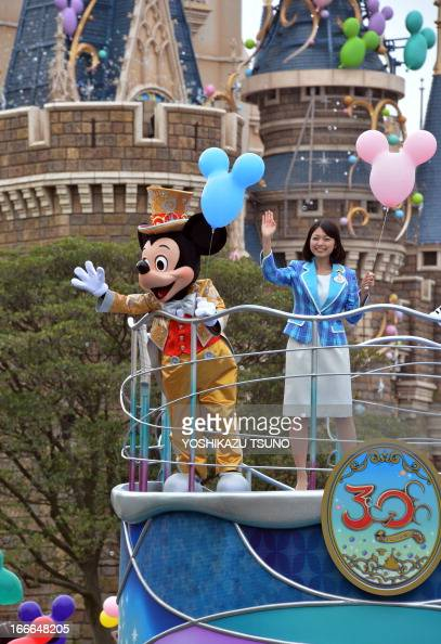 Mickey Mouse and Disney Resort Disney ambassador Ayaka Nagai wave their hands from a float for the parade as the Tokyo Disneyland celebrates its 30th...