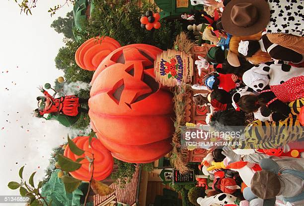 Mickey mouse appears atop a pumpkin float while receiving cheers from costumed guests during the Tokyo Disneyland's Happy Halloween Pumpkin Parade 31...