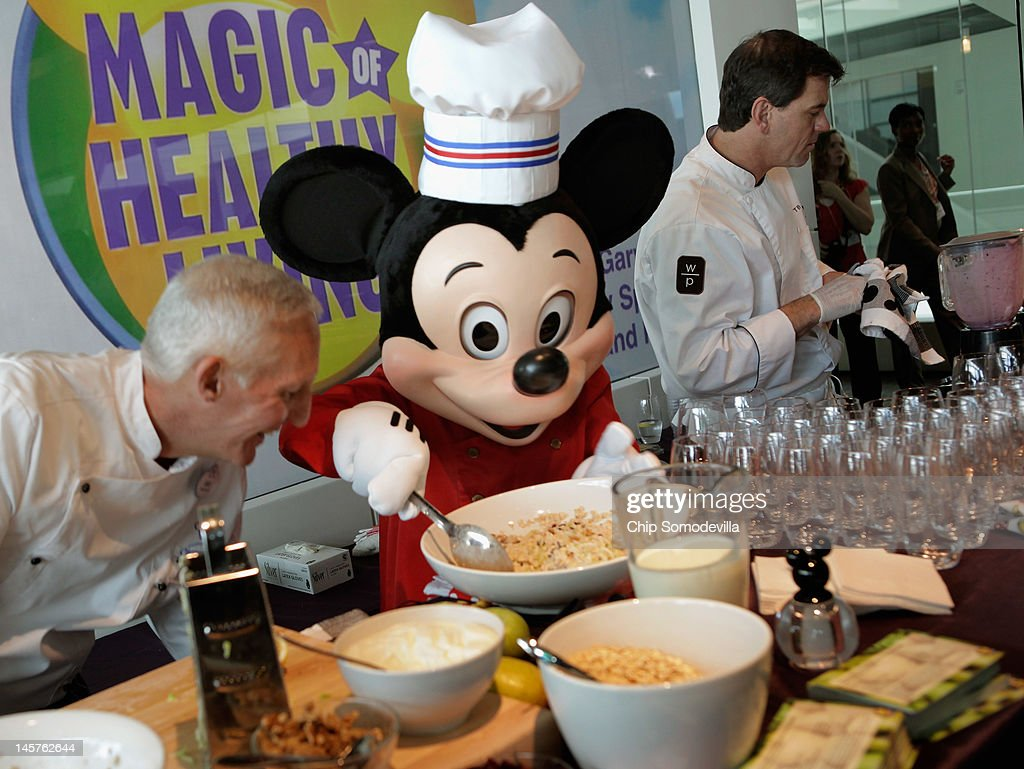 A Mickey Mouse character assists Walt Disney Parks and Resorts Culinary Dietary Specialist Gary Jones (L) make healthy smoothies during an event introducing Disney's new 'Magic of Healthy Living' program at the Newseum June 5, 2012 in Washington, DC. As part of the new healthy eating initiative, all products advertised on Disney's child-focused television channels, radio stations and Web sites must adhear to a new set of strict nutritional standards. Addionally, Disney-licensed products that meet criteria for limited calories, saturated fat, sodium and sugar can display a logo - Mickey Mouse ears and a check mark - on their packaging.