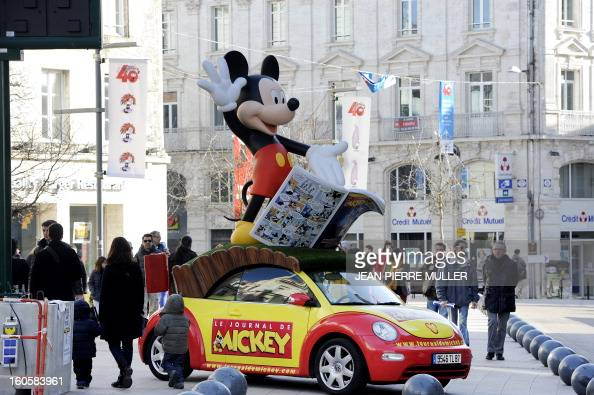 A Mickey mouse giant figurine fixed on the roof of a car is exhibited in the streets on the last day of the Comic book festival of Angouleme on...
