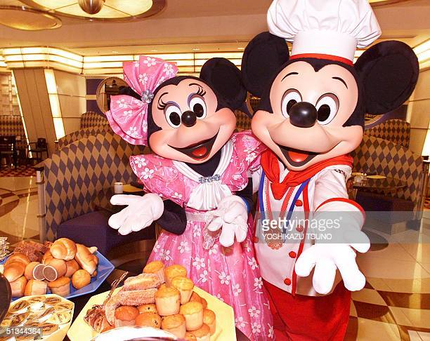 Mickey Mouse in chef's uniform accompanied by Minnie Mouse display a heap of breads on a plate during a press preview at a restaurant of the newly...