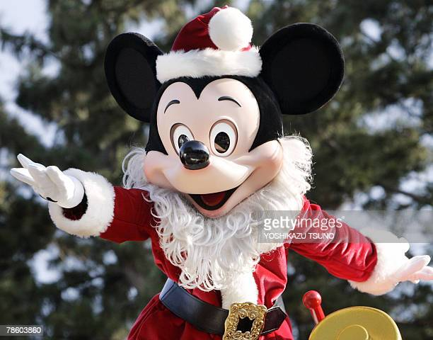 Mickey Mouse in Santa Claus outfit waves in front of the castle during a parade at Tokyo Disneyland at Urayasu city in Chiba prefecture 21 December...