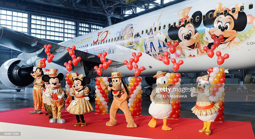 Mickey Mouse (2nd L), Minnie Mouse (3rd L) and other Disney character mascots introduce a Boeing 777-200 plane decorated with Disney characters (back) at a hangar of Japan Airlines at Haneda Airport in Tokyo on March 29, 2013. JAL unveiled the special plane for domestic flights on March 29, ahead of the 30th anniversary of the Tokyo Disneyland on April 15. AFP PHOTO / Toru YAMANAKA