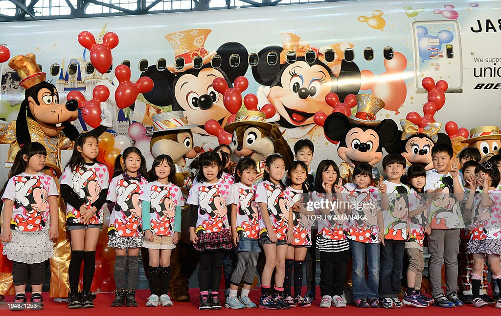 Mickey Mouse (back 3rd R), Minnie Mouse (back 2nd R) and other Disney characters pose with local elementary school children during a ceremony to introduce a Boeing 777-200 plane decorated with Disney characters (top) at a hangar of Japan Airlines at Haneda Airport in Tokyo on March 29, 2013. JAL unveiled the special plane for domestic flights on March 29, ahead of the 30th anniversary of the Tokyo Disneyland on April 15. AFP PHOTO / Toru YAMANAKA