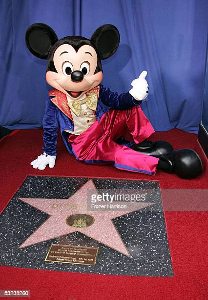 Mickey Mouse poses in front of the Disneyland star of Excellence presented by the Hollywood Historic Trust to mark Disneylands 50th anniversary...