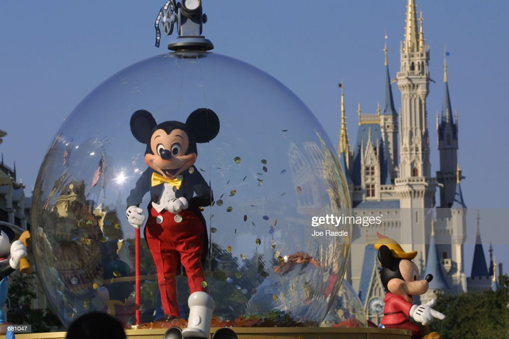 Mickey Mouse rides in a parade through Main Street USA with Cinderella's castle in the background at Disney World's Magic Kingdom November 11 2001 in...