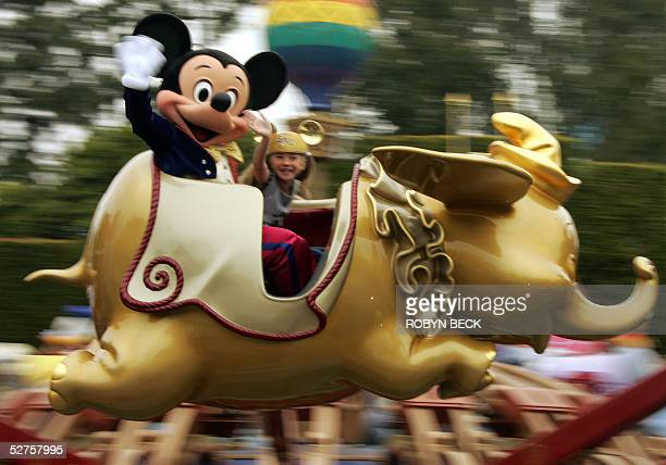 Mickey Mouse rides on a golden Dumbo with Caroline Sunshine age nine on the Disney 50th anniversary press preview day at Disneyland in Anaheim CA 04...