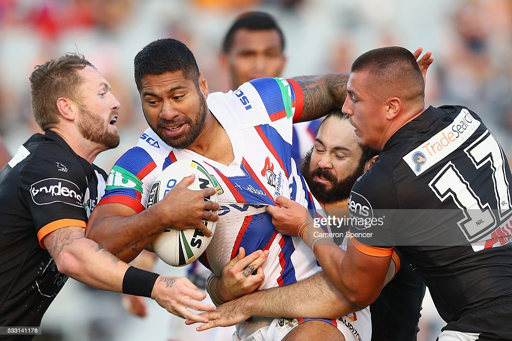 Mickey Paea of the Knights is tackled during the round 11 NRL match between the Wests Tigers and the Newcastle Knights at Campbelltown Sports Stadium...
