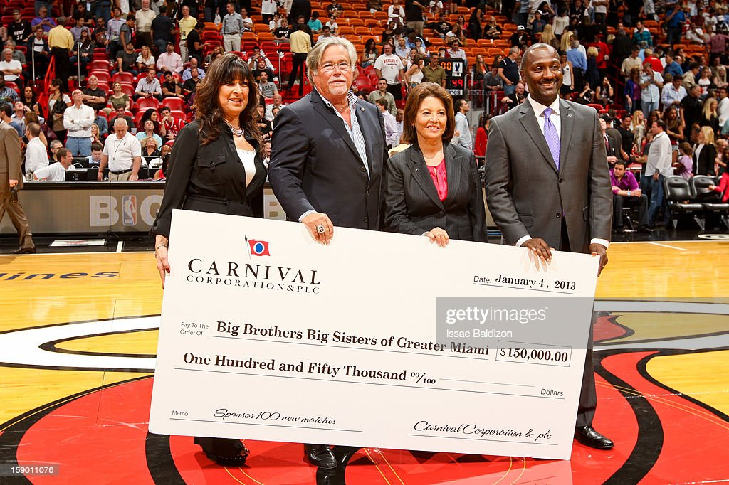 Micky Arison, chief executive officer of Carnival Corp. and owner of the Miami Heat, second left, presents a check to the Big Brothers Big Sisters of Greater Miami organization during a game between the Heat and Chicago Bulls on January 4, 2013 at American Airlines Arena in Miami, Florida.