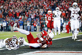 Micky Crum of the Louisville Cardinals makes a twoyard touchdown reception against the Texas AM Aggies in the first quarter of the Franklin American...
