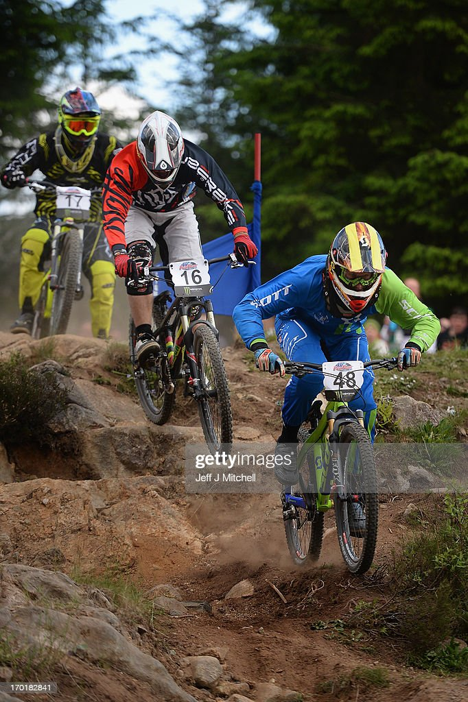 Micro Weiss, Alexander Metcalfe and Jordan Lunn compete in the men's four cross pro tour qualification at the UCI Mountain Bike World Cup on June 8, 2013 in Fort William, Scotland.