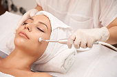 Cosmetologist using microdermabrasion machine for peeling, view from above
