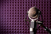 A microphone in a purple recording studio