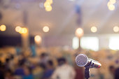 Microphone in concert hall or conference room soft and blur style for background.Microphone over the Abstract blurred photo of conference hall or seminar room background.