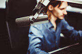 Microphone in radio studio and presenter on background