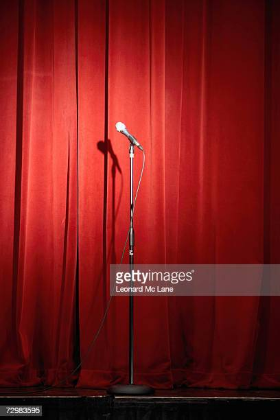 Microphone on stage against red curtain