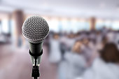 Microphone on boom stand ready for the meeting ,blurred background group of people sitting around table. Microphone on stage in conference hall.