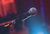 Microphone on the stage on blue and red dark background.