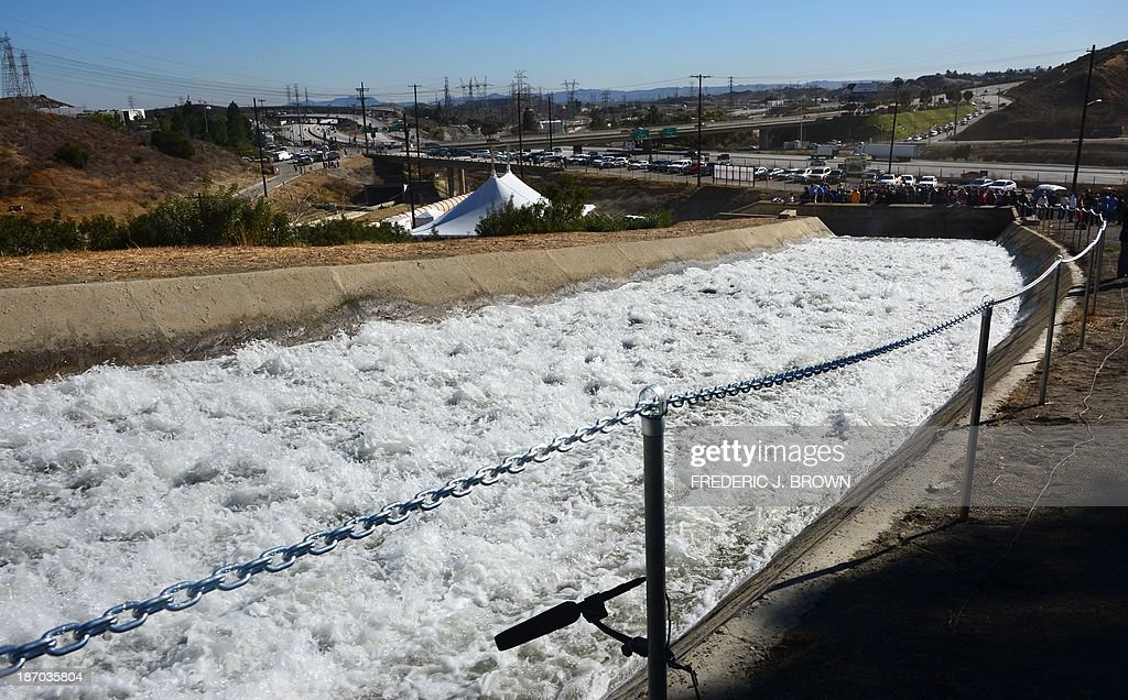 A microphone records the sounds of gushing water flowing following a re-enactment of the moment the Los Angeles Aqueduct gates were first opened 100 years ago, on November 5, 2013 in Sylmar, California, sending water gushing towards the city during an event marking the 100th anniversary of the opening of the 233-mile Los Angeles Aqueduct, which transports water from the Owens Valley to Los Angeles. The aqueduct started bringing water from the Owens River on the eastern slope of the Sierra Mountains to Los Angeles in November 1913 and the massive public works project is widely credited with transforming Los Angeles from a sleepy agricultural town into a modern metropolis, allowing for the city's rapid expansion. AFP PHOTO/Frederic J. BROWN