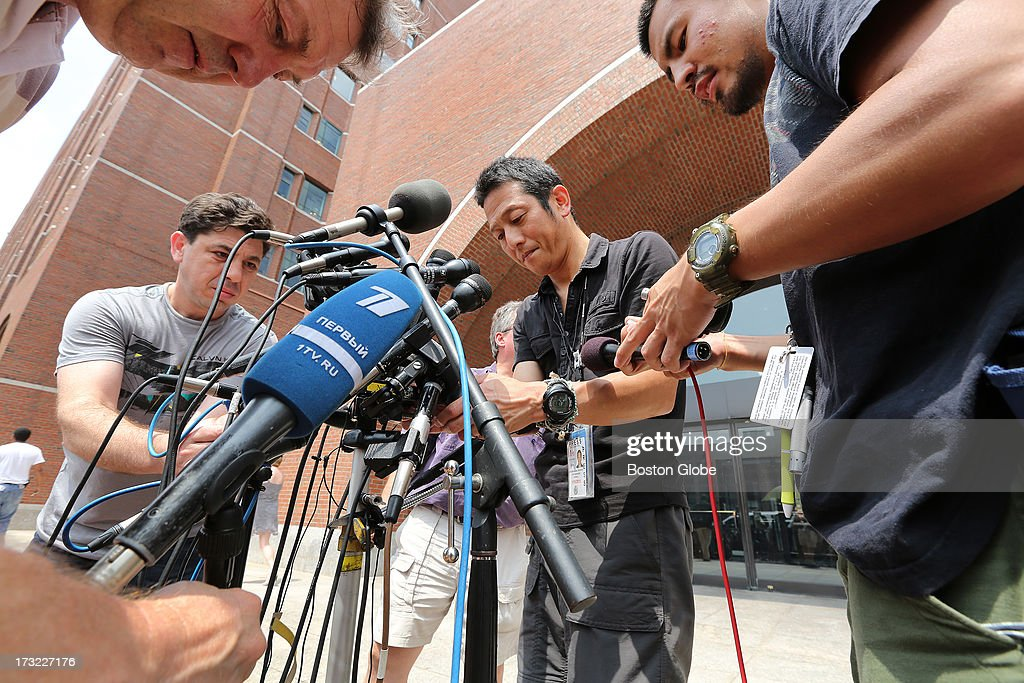 Microphones are set up for a press conference, including one for Russia's Channel 1 (in blue). The media gathers outside the John Joseph Moakley United States Courthouse before Boston Marathon bombings suspect Dzhokhar Tsarnaev is charged, July 10, 2013.
