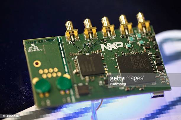 Microprocessors sit on a circuit board displayed on the NXP Semiconductors NV pavilion at the Mobile World Congress in Barcelona Spain on Monday...