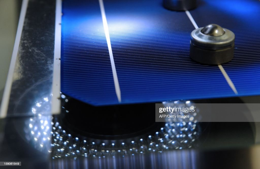 A microscope controls a photovoltaic cell on an assembly line at MPO Energy plant in Averton, western France, on January 7, 2013.