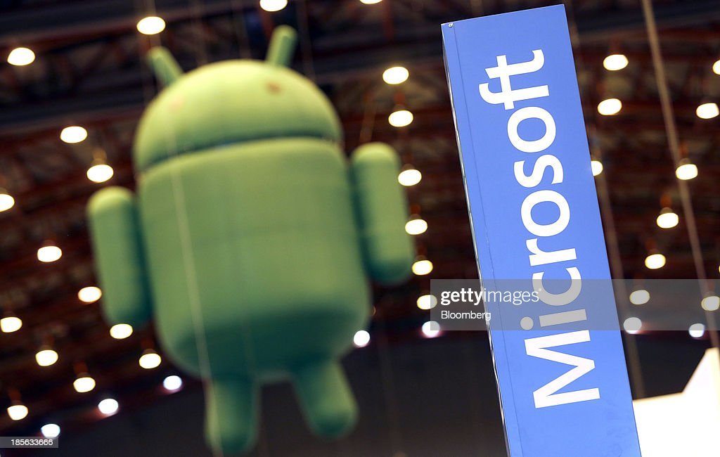 A Microsft Corp. logo stands on the company's display booth near a giant inflatable Android, the symbol of Google Inc.'s mobile operating system, during the Apps World Multi-Platform Developer Show in London, U.K., on Wednesday, Oct. 23, 2013. Retail sales of Internet-connected wearable devices, including watches and eyeglasses, will reach $19 billion by 2018, compared with $1.4 billion this year, Juniper Research said in an Oct. 15 report. Photographer: Chris Ratcliffe/Bloomberg via Getty Images