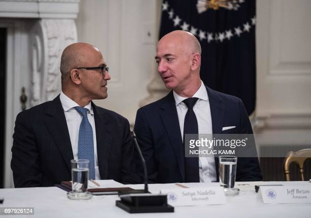 Microsoft CEO Satya Nadella and Amazon CEO Jeff Bezos chat during an American Technology Council roundtable at the White House in Washington DC on...