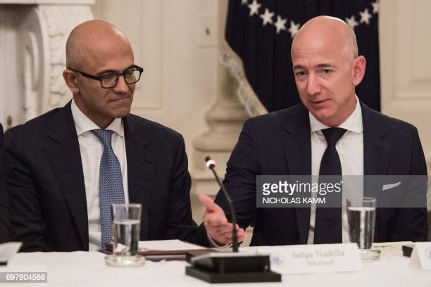 Microsoft CEO Satya Nadella listens to Amazon CEO Jeff Bezos during an American Technology Council roundtable at the White House in Washington DC on...