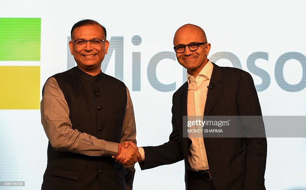 Microsoft CEO Satya Nadella (R) shakes hand with Indian Minister of State for Finance Jayant Sinha during a Microsoft event in New Delhi on May 30, 2016. Nadella met with Indian developers and tech entrepreneurs on his visit to India. / AFP / MONEY