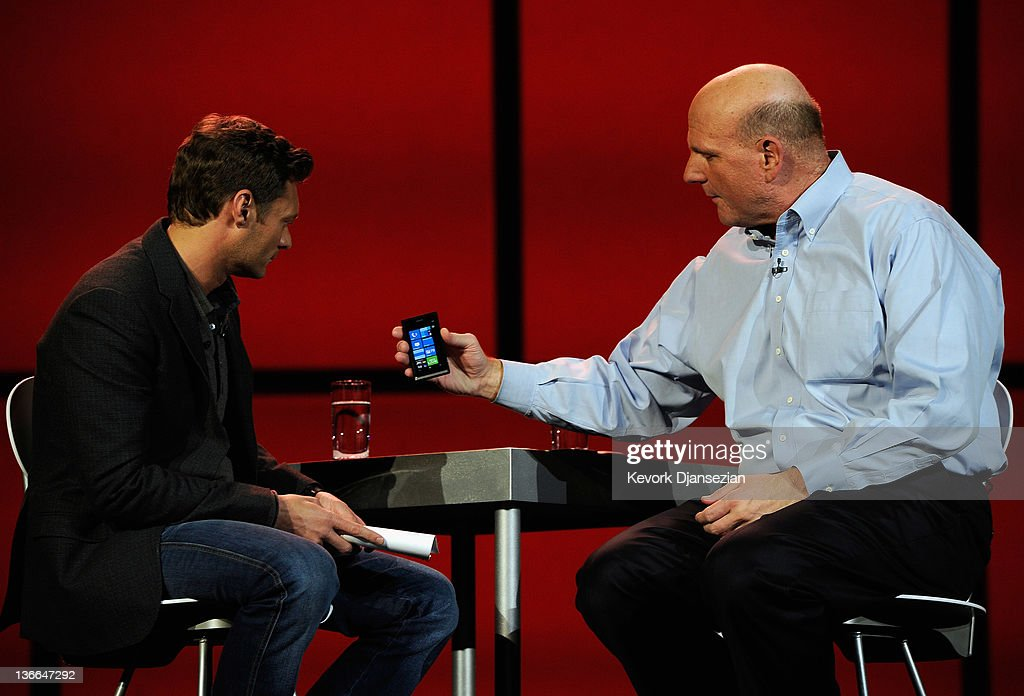 Microsoft CEO Steve Ballmer (R) shows the new windows phone to host Ryan Seacrest during Ballmer's keynote address at the 2012 International Consumer Electronics Show at The Venetian January 9, 2012 in Las Vegas, Nevada. CES, the world's largest annual consumer technology trade show, runs through January 13 and is expected to feature 2,700 exhibitors showing off their latest products and services to about 140,000 attendees.