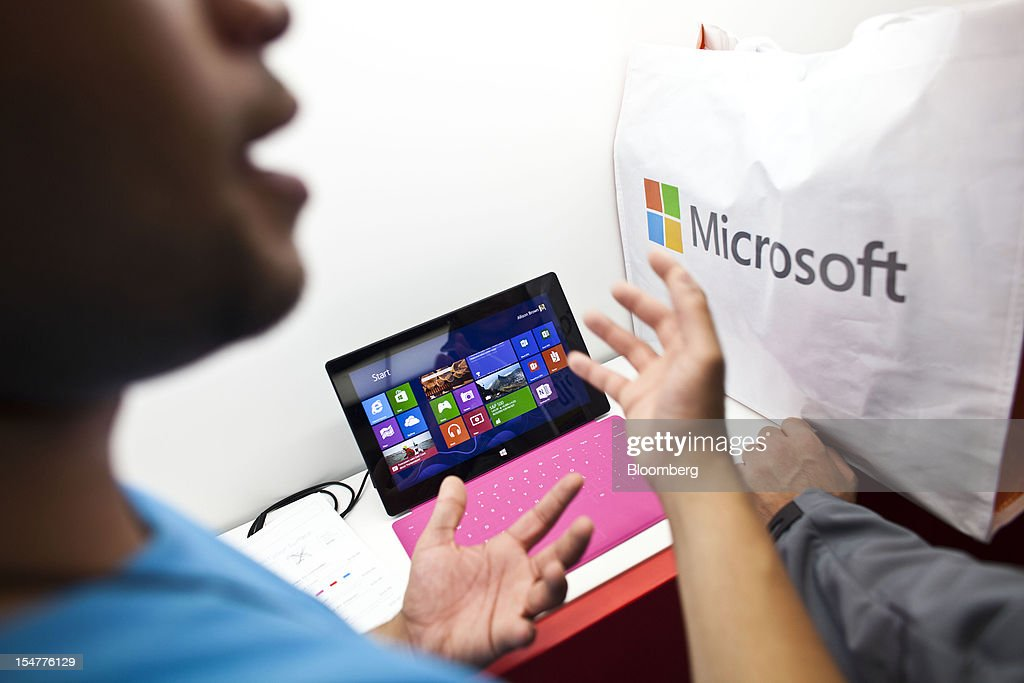 A Microsoft Corp. employee assists a customer as a Surface tablet sits inside the company's store during its grand opening in New York, U.S., on Thursday, Oct. 25, 2012. Microsoft Corp. introduced the biggest overhaul of its flagship Windows software in two decades, reflecting the rising stakes in its competition with Apple Inc. and Google Inc. for the loyalty of customers who are shunning personal computers and flocking to mobile devices. Photographer: Ramin Talaie/Bloomberg via Getty Images