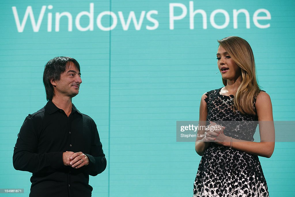 Microsoft Corporate Vice President Joe Belfiore (L) listens as actress <a gi-track='captionPersonalityLinkClicked' href=/galleries/search?phrase=Jessica+Alba&family=editorial&specificpeople=201811 ng-click='$event.stopPropagation()'>Jessica Alba</a> speaks during a Windows Phone 8 product launch at Bill Graham Civic Auditorium on October 29, 2012 in San Francisco, California. The Windows Phone 8 marks the Seattle-based company's latest update from its two-year-old Windows Phone 7 platform as the company looks to regain its traction in the increasingly dense smartphone segment dominated by rivals Apple and Google.