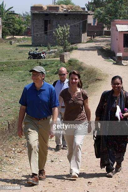 Microsoft founder and philanthopist Bill Gates and his wife Melinda walk during a visit to Jamsaut villages at Patna district in India's Bihar's...