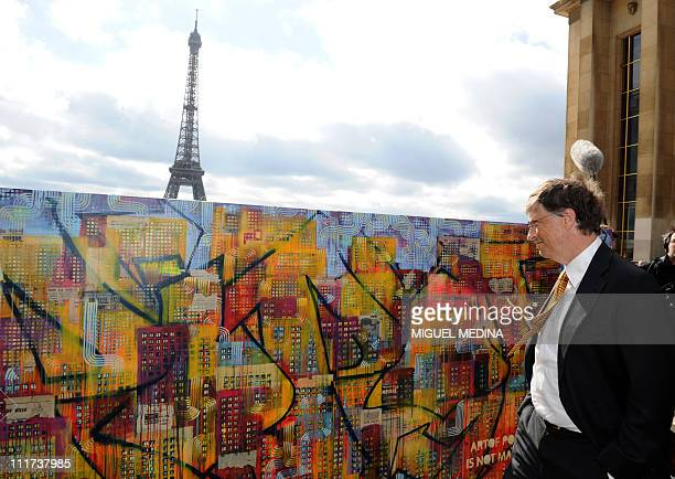 Microsoft founder and philanthropist Bill Gates looks at a painting of two artists Dag and Russian Artof Popof on April 4 2011 at the Trocadero in...