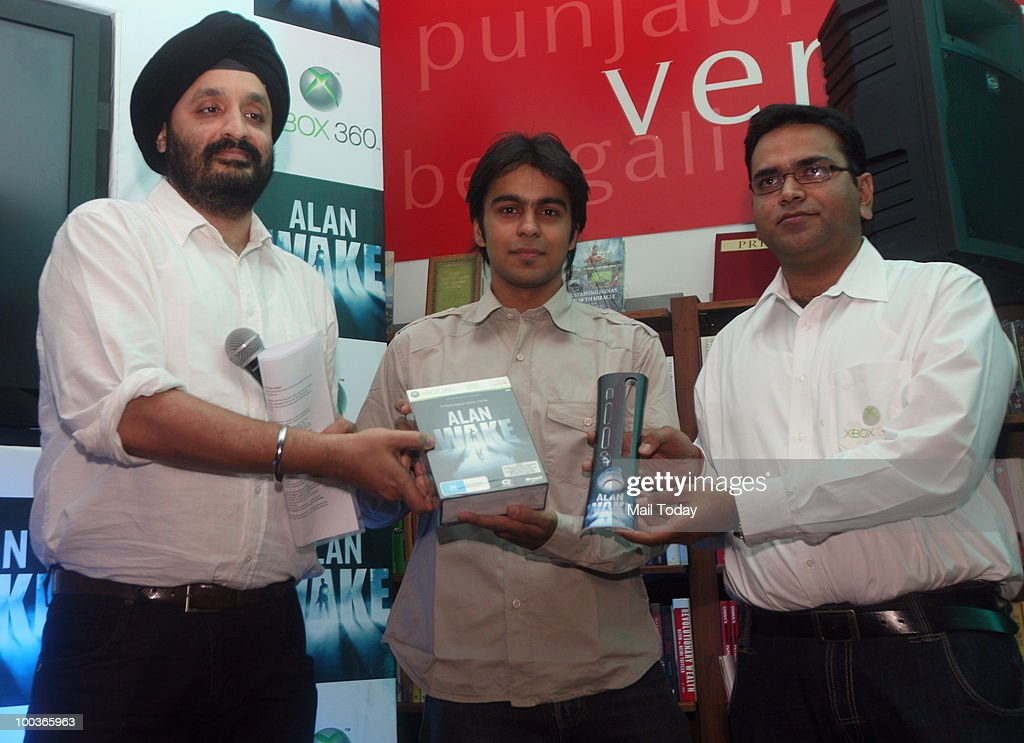 Microsoft India's Jaspreet Bindra(L) and Ashim Mathur(R) hand an Alan Wake game, the much-awaited game from Microsoft for its Xbox 360 gaming platform, title to gamer Abhishek at its India launch in New Delhi on May 20, 2010.