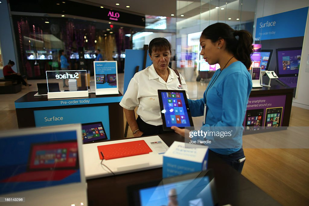 Microsoft Product Advisor Daniela Belevanon (R) helps Marta Aranda as she looks at a Surface tablet loaded with the Windows 8.1 operating system at a Microsoft store in the Dadeland Mall October 17, 2013 in Miami, Florida. The update was released a year after Windows 8 was released and includes fixes to some of the problems people experienced with the initial release.