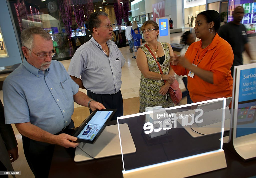Microsoft Product Advisor Michelle Mckenzie (R) helps Amparo Nader (2nd R) and Marcelo Nader (2nd L) look at a Surface tablet loaded with the Windows 8.1 operating system at a Microsoft store in the Dadeland Mall October 17, 2013 in Miami, Florida. The update was released a year after Windows 8 was released and includes fixes to some of the problems people experienced with the initial release.