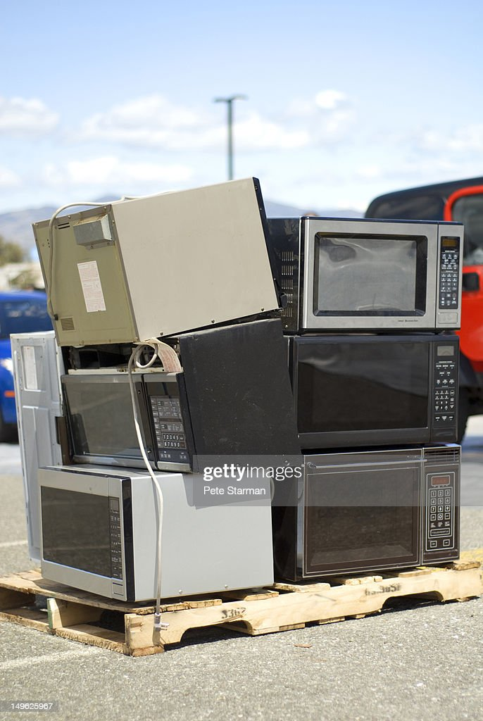 Microwave ovens stacked up at an e-waste center : Stock Photo